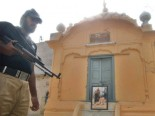 A policeman guards at a Sikh temple that a Islamic group  claims is the burial site of a Muslim saint.  Pic : The Express Tribune.
