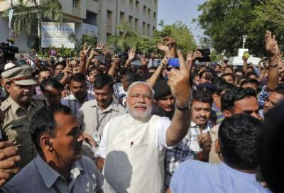 Hindu nationalist Modi shows his ink-marked finger to his supporters after casting his vote in Ahmedabad