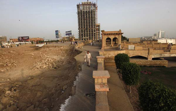 A man walks past the construction of an underpass and a flyover near the 150-year-old Shri Ratneshwar Mahadev temple