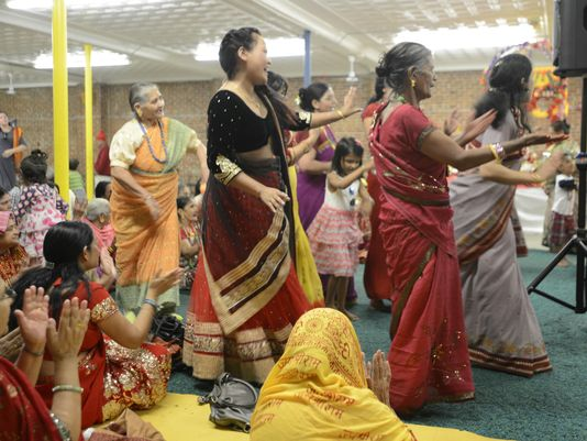 A group of women dances to music as others seated clap and sing along during a Puran celebration in Burlington on Sunday. (Photo: ELIZABETH MURRAY/FREE PRESS)