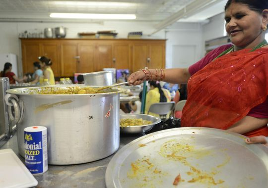 Rupa Poudyel prepares food to be served during the last of three days of a Puran celebration held in Burlington on Sunday. (Photo: ELIZABETH MURRAY/FREE PRESS)