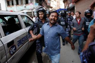 Nepalese police detain a protester during a demonstration against the government and the new constitution during in Kathmandu, Nepal, Sunday, Sep 20, 2015. Police quickly dispersed the protest and two people were detained. Police were under orders to stop any protests. Schools and offices are closed because Sunday and Monday were declared a public holiday to celebrate the constitution, Nepal's first complete political framework since monarchy was abolished in 2006. (AP Photo/Niranjan Shrestha)