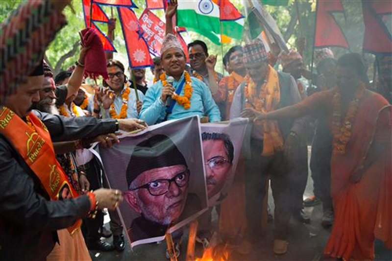 Nepali burn portraits of Nepal's Prime Minister Sushil Koirala (left) and Communist Party of Nepal (Maoist) Chairman Pushpa Kamal Dahal during a protest against its government, in New Delhi, India on Tuesday, September 22, 2015. Photo: AP.