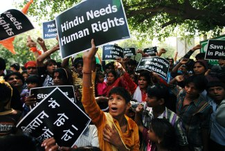 Pakistani Hindus hold placards as they shout slogans during a protest against alleged human rights violations in Pakistan, outside the United Nation office in New Delhi, India, Wednesday, April 17, 2013. A group of Hindus from Sindh province in Pakistan are living in India after leaving their home country a year ago for fear of being persecuted, according to news reports. (AP Photo/Altaf Qadri)