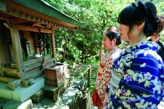 Women worshipping in front of Benzaiten (Saraswati) Temple  in Japan.