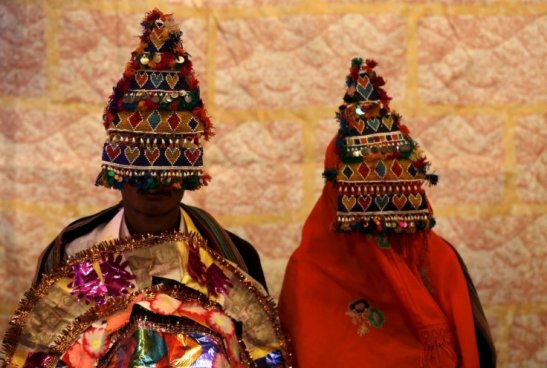 A bride and groom wearing traditional handmade garlands wait for their wedding to start during a mass marriage ceremony in Karachi, Pakistan.Akhtar Soomro/Reuters file photo.