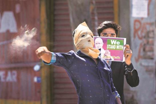 A masked Kashmiri protester throws a rock at policemen, as another holds a poster in support of Islamic preacher Zakir Naik, in Srinagar, India, Friday, July 8, 2016. Dozens of youth in the Indian portion of Kashmir clashed with policemen during a protest against the allegations that Naik was involved in making hate speeches. (AP Photo/Dar Yasin)