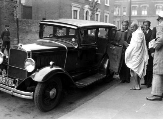 UNITED KINGDOM - SEPTEMBER 26: Mahatma Gandhi in London, 2 October 1931. Gandhi entering a car outside Kingsley Hall. Gandhi (1869-1948) is remembered for his civil disobedience policy against British rule in India and his belief in non-violent protest. Gandhi was involved in negotiations with the British over Indian independence. In 1931, he came to London to attend the Round Table conference on Indian constitutional reform and in 1946 he was involved in the new constitutional structure for independent India. He was assassinated in September 1948. Photograph by Harold Tomlin. (Photo by Daily Herald Archive/SSPL/Getty Images)