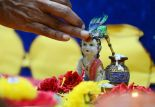 An Indian school teacher marks a statue of Hindu god, Lord Krishna with kumkuma on the occasion of Janamashthami, the birthday of Lord Krishna, in Hyderabad on August 25, 2016. Janmashtami celebrates the birth of one of the most popular Gods of Hindu religion, Lord Krishna. / AFP PHOTO / NOAH SEELAM