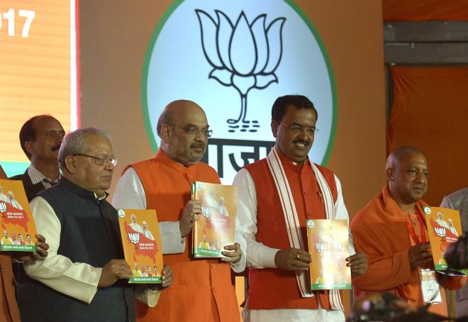 BJP president Amit Shah (second from left) releases the BJP manifesto for the U.P. Assembly elections, in Lucknow on Saturday. Union Minister Kalraj Mishra (left), U.P. BJP chief Keshav Prasad Maurya (third from left) and Gorakhpur MP Yogi Adityanath are also seen in the picture. | Photo Credit: Rajeev Bhatt.